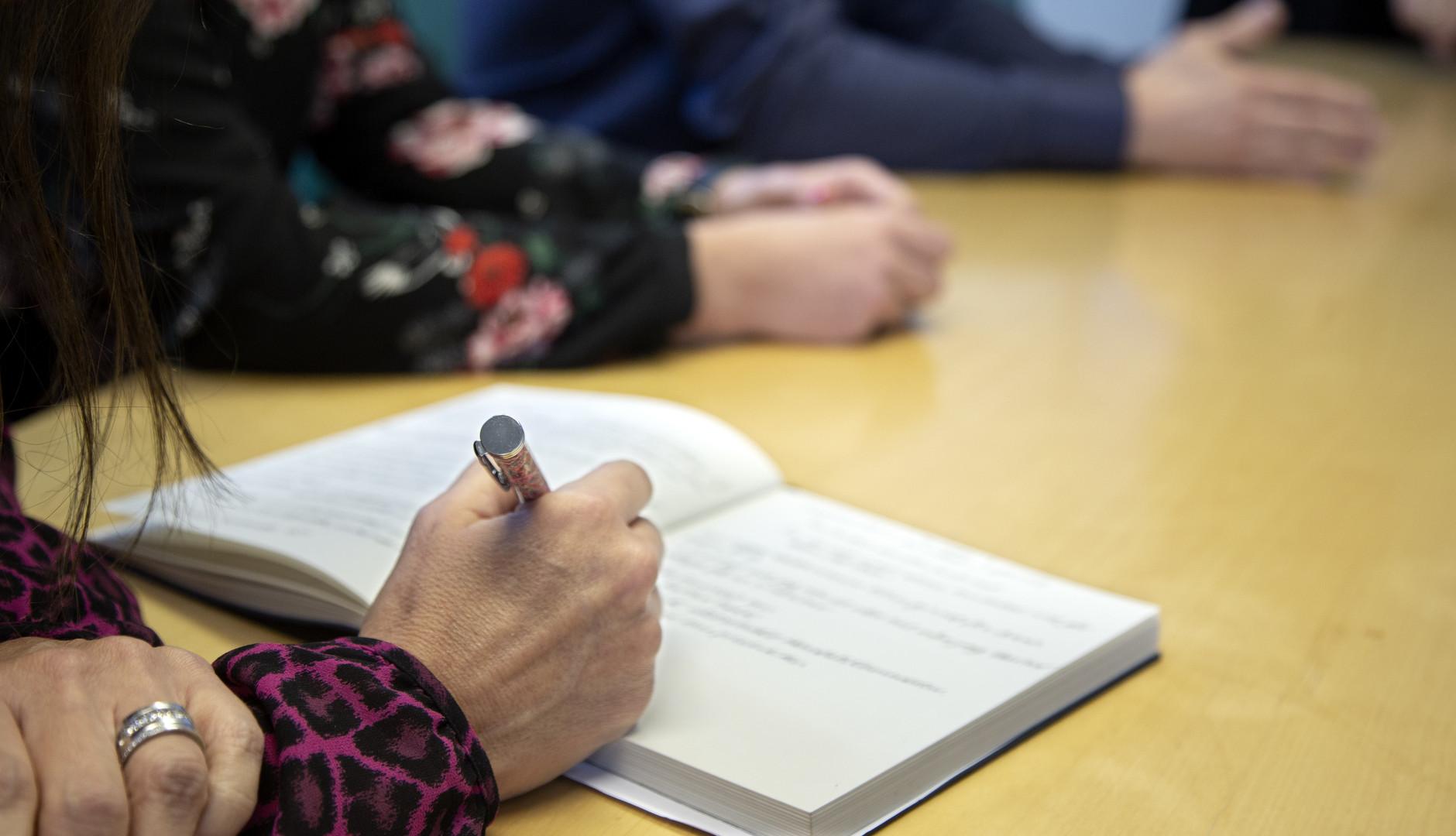 Möte med kvinna som antecknar på block med bläckpenna
