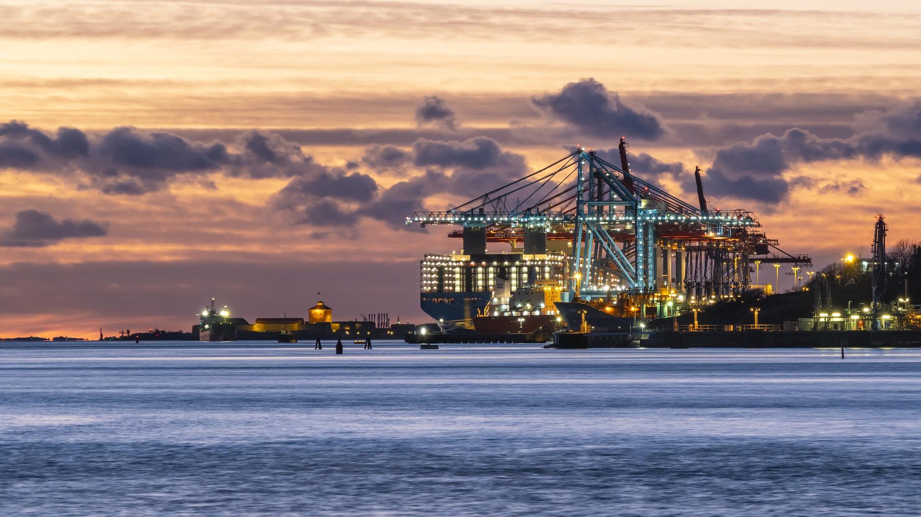 Containerfartyg och hamnkranar i kvällsljus med Nya Älvsborgs fästning i bakgrunden