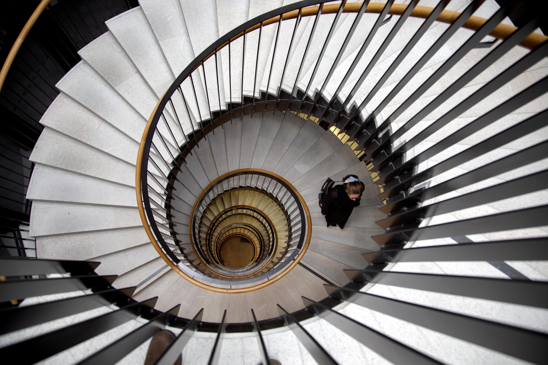 Kvinna påväg upp i spiraltrappa vy uppifrån