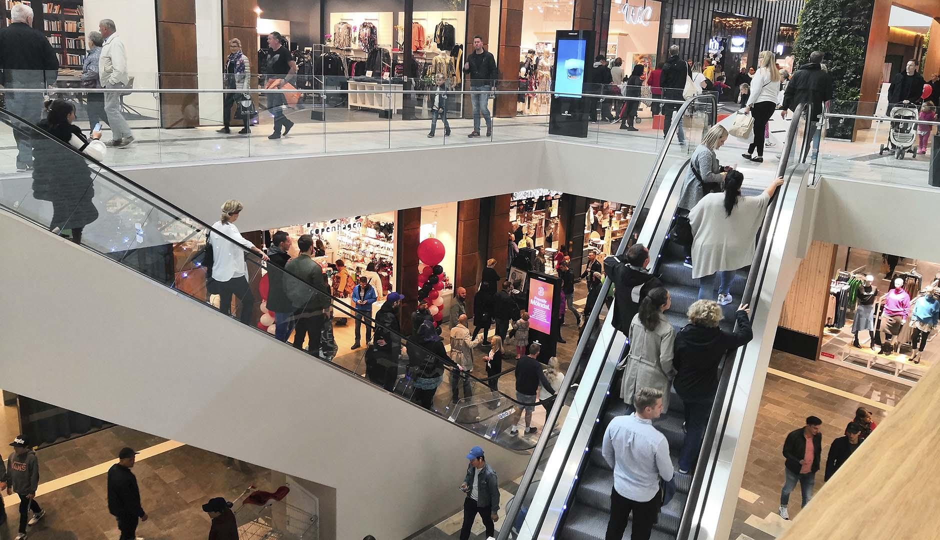 Rulltrappor med människor i köpcentrum